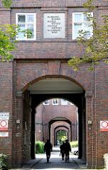 Passanten gehen durch einen Torweg in Hamburg Dulsberg - Wohngebäude in den Hamburger Stadtteilen; Fotos der Hamburger Architektur.