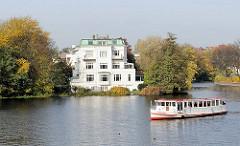 Historische weisse Villa  zwischen Herbstbäumen an der Alster. Ein Alsterdampfer wendet vor dem Eichenpark in Hamburg Harvestehude.
