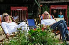 Beachclub im Landhaus Walter am Hamburger Stadtpark - die Gäste geniessen in Liegestühlen und Strandkörben die Sonne.