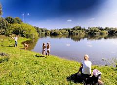 Sommeridylle im Höltingbaum - eine Familie sitzt am Seeufer; die Kinder sehen zu wie der Hund am See spielt.