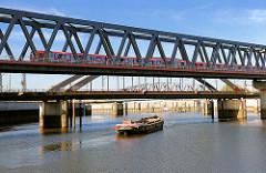 S-Bahnzug in Fahrt auf der Eisenbahnbrücke über den Oberhafenkanal / Billehafen in Hamburg Rothenbursort; eine Schute wird auf dem Kanal von einer Barkasse gezogen.