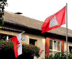 Flaggen der Hansestadt Hamburg und dem Bezirk Harburg an einem Gebäude von Hamburg Rönneburg.