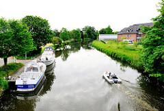 Boote auf der Doveelbe festgemacht am Steg  in Hamburg Curslack; ein Motorboot fährt Richtung Neuengamme.