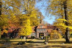 Wellingsbüttler Torhaus im Herbst - Herbstbäume und Laub auf der Wiese.