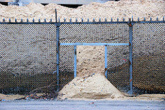 Zollzaun zum Hamburger Freihafen - Eisenzaun, Maschendrahtzaun mit Spitzen und Stacheldraht an der Versmannstrasse. Sand ist hinter dem Zaun hoch aufgeschüttet und strömt durch ein Loch im Zaun.