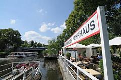 Schild Winterhuder Fährhaus - Café auf dem Ponton; sitzen am Wasser in der Sonne.