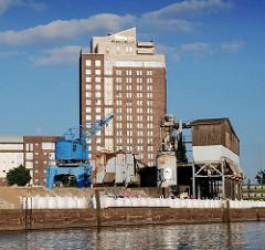 Blick vom Billhafen über die Kaianlagen zum Hotelhochhaus in Hamburg Rothenburgsort. Auf dem Hafenkai steht ein blauer Hafenkran und Verladeeinrichtungen für Schüttgut.