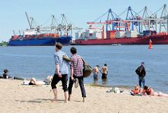 Elbufer in Hamburg Othmarschen - Spaziergänger barfuss im Sand, ander stehen im Wasser oder sonnen sich im Elbsand; im Hintergrund Containerschiffe am Terminal Burchardkai.