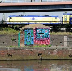 Grafitti am Bunker des Billehafens, Oberhafenkanal - im Hintergrund eine Lokomotive der Metronom.