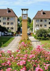 Wohnanlage Rosentreppe - blühende Rosen, Uhr auf gelber Klinkersäule - Gebäude Eisenbahn Bauverein Harburg.