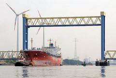 Kattwyckbrücke an der Süderelbe - das Mittelteil der Hubbrücke ist hochgefahren, ein Frachtschiff fährt mit Schlepperunterstützung auf der Süderelbe.
