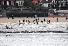 Eisgang auf der Elbe - Eisschollen am Ufer der Elbe - Spaziergänger und spielende Kinder.