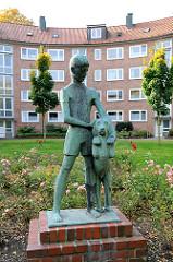 Bronzeskulptur - Junge mit Hund im Innenhof eines Nachkriegsgebäudes in Hamburg Barmbek Süd.