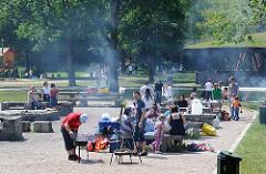 Grillplatz in Hamburg Rissen - Sandkuhle; die Besucher sitzen auf Bänken, die Grills qualmen.