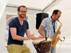 Musiker mit Trommel und Saxophon spielen unter einem Zeldach auf dem Bauernmarkt vom Biogut Wulksfelde.