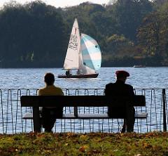Segeln als Freizeitspass in Hamburg - Segelboot mit gesetztem Spinnaker auf der Aussenalster - Herbstlaub auf der Wiese.