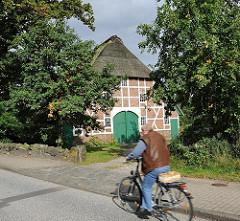 Fachwerkscheune mit Reet gedeckt - Fahrradfahrer auf der Francoper Strasse.