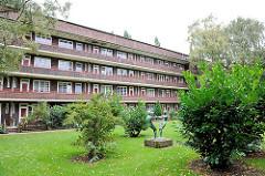 Innenhof mit Wiese und Büschen - Wohngebäude mit Laubengängen in Hamburg Dulsberg.