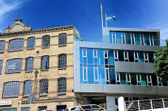 Historisches Gebäude der Maschinenfabrik Groth & Degenhardt - futuristischer Neubau mit Metallfassade im Sonnenlicht.