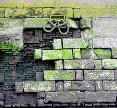 Alte, teilweise zerstörte Kaimauer im Hamburger Hafen; große Eisenschäkel zum Festmachen von Schiffen sind durch einen eingelassenen Ring geführt.