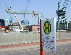 Bushaltestelle der Sietas Werft - Werfkräne im Hintergrund, Kopfsteinpflaster auf der Strasse.