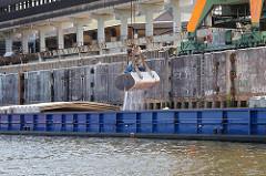 Der Greifer holt das Schüttgut / Kali aus dem Laderaum des Binnenschiffs am Wilhelmsburger Kalikai.