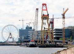 Schwimmkräne montieren ein Brückenteil der Baakenhafenbrücke am Versmannkai in der Hamburger Hafencity.