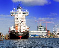 Frachtschiff auf Reede an den Dalben in der Norderelbe - im Hintergrund Gebäude der Hafencity Hamburgs.