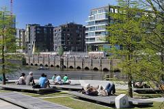 Hamburger und Touristen sitzen an den Marco Polo Terrassen und blicken auf die moderne Architektur am Dalmannkai.