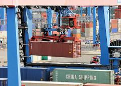 Portalkran des Containerbahnhofs auf dem Areal des Container Terminals Altenwerder - ein Container wird über den Güterwagen transportiert - in einer Kanzel sitzt der Kranführer.