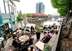 Blick vom Kai des Hafens von Hamburg Bergedorf - Gäste eines Restaurants sitzen in der Sonne am Wasser - im Hintergrund ein Einkaufszentrum.