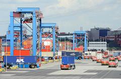 Automated Guided Vehicle (AGV) bei ihrer Arbeit - einige warten leer auf den Befehl zur Weiterfahrt, um die Containerladung aufzunehmen, ander bringen den Stahlbehälter zu den Portalkränen.