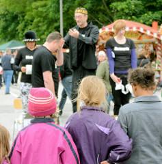 Kinder sehen einer Strassentheatergruppe bei ihrem Auftritt auf dem Hafenfest von Hamburg Harburg zu.