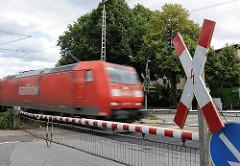 Bahnübergang Hammer Strasse - heruntergelassene Bahnschranken mit Andreaskreuz - eine Güterzuglokomotive fährt vorbei.
