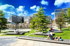 Sommer in Hamburg - Grünanlager mit Liegeflächen im Marco-Polo Platz in der Hamburger Hafencity - Gebäude am Dalmannkai.