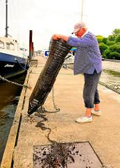 Eine ausgelegte Metallreuse wird von dem Fischer aus dem Wasser geholt.