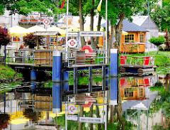Anleger und Biergarten, Gastwirtschaft am Ernst August Kanal - Sonnenschirme und Tische im Garten am Kanalufer.