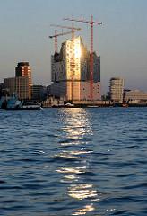 Abendsonne im Hamburger Hafen - die untergehende Sonne spiegelt sich in der Glasfassade der entstehenden Elbphilharmonie in der Hamburger Hafencity.