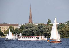 Segelboote und das Fahrgastschiff / Alsterdampfer Ammersbek auf der Aussenalster - im Hintergrund der Kirchturm der St. Gertrudenkirche in Hamburg Hohenfelde.