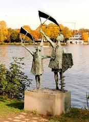 """Skulptur """"Drachensteigenlassende Kinder"""" - Bildhauer  Gerhard Brandes / 1963; aufgestellt am Alsterufer in Hamburg Harvestehude - im Hintergrund Herbstbäume an der Alster."""