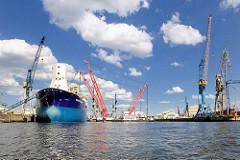 Werfthafen Blohm + Voss im Hamburger Hafen - Schiffsneubau; Schwimmkran RAMBIZ beim Transport / Einbau eines Schiffsteils.