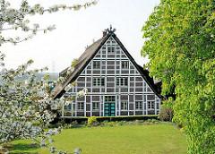 Fachwerkgebäude mit Reet gedeckt - blühender Obstbaum, Hamburg Fracop im Frühling.