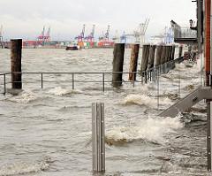 Das Hochwasser ist über die Kaimauer bei der Grossen Elbstrasse gestiegen und hat einen Fussgängersteg überschwemmt - Wellen schlagen gegen die Hauswand.