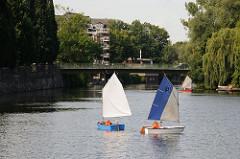 Kinder mit Schwimmwesten lernen auf dem Alsterkanal in kleinen Dingis segeln.