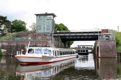 Ein Fahrgastschiff kommt aus der Krapphof Schleuse und fährt in die Doveelbe ein - im Hintergrund wartet eine weitere Barkasse und ein Sportboot auf die Ausfahrt.