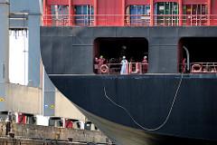 Ein Besatzungsmitglied wirft die Bolaleine, an der die Festmacherleine befestigt ist, mit der das Schiff an den Eisenpollern vertäut wird.
