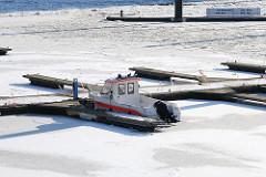 City Sporthafen Hamburg im Winter; ein Sportboot liegt im Eis am Steg des Cityhafens.