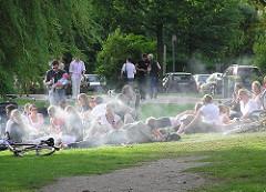 Grillzeit in Hamburg - Jugendliche grillen im Alstergrün - Rauchschwaden ziehen durch die Grünanlage.
