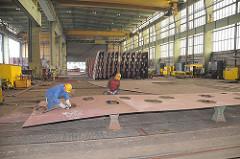 Werftarbeiter arbeiten in der Werkhalle an einer grossen Stahlplatte.