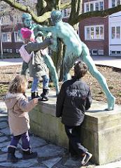 """Schulkinder turnen auf der Bronzeskulptur """"Faustkämpfer"""" voM Bildhauer Eberhard Encke, geschaffen 1913."""